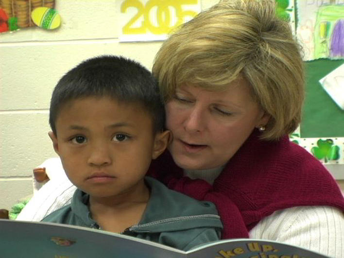 Boy from Burma with his teacher at school