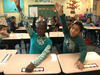 Children raising their hands in elementary school